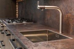 Golpecito de agua moderno del cromo del diseñador sobre fregadero de cocina del acero inoxidable foto de archivo