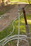 Golpecito de agua oxidado viejo con la manguera en jardín Imagen de archivo libre de regalías