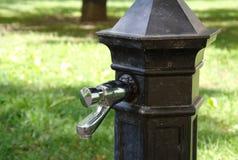 Golpecito de suministro de agua tradicional con agua potable en el parque imagenes de archivo