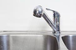 Golpecito y fregadero de agua de la cocina Imagen de archivo