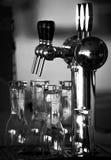 Golpecito y vidrios de la cerveza listos para servir algunas pintas Fotos de archivo libres de regalías