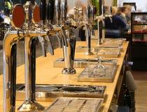 Golpecitos de la cerveza en el contador de un pub irlandés imagen de archivo libre de regalías