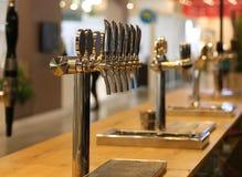 Golpecitos de la cerveza en el contador de un pub irlandés imagenes de archivo