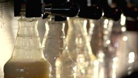 Golpecitos de la cerveza que llenan las botellas plásticas almacen de video