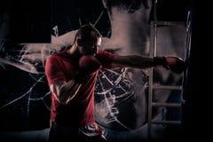 Golpee el boxeo del boxeador con el pie como ejercicio para la lucha grande El boxeador golpea el saco de arena Trenes jovenes de Imagenes de archivo