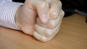 Golpeo masculino de la mano en la tabla metrajes