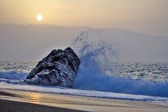 Golpes de la onda del mar en la roca contra la puesta del sol imagen de archivo libre de regalías