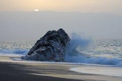 Golpes de la onda del mar en la roca contra la puesta del sol fotografía de archivo