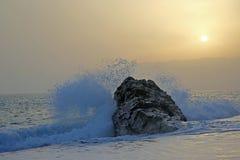 Golpes de la onda del mar en la roca contra la puesta del sol foto de archivo libre de regalías