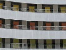 3 golv av olika färgade dörrar i byggnadsfasad Royaltyfria Foton