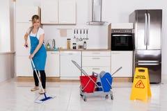 Golv för kvinnalokalvårdkök med golvmopp Royaltyfri Foto