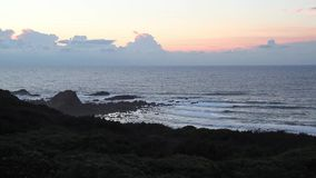 Golven bij de kust van de Atlantische Oceaan tijdens een mistige zonsondergang stock videobeelden