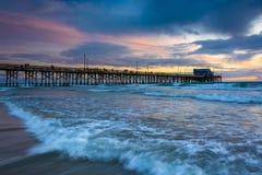 Golven in de Vreedzame Oceaan en de Pijler van Nieuwpoort bij zonsondergang Royalty-vrije Stock Afbeeldingen