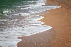 Golven die aan het zandige strand rollen Stock Afbeeldingen