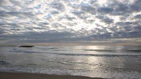 Golven die bij het strand met bewolkte hemel aankomen stock footage