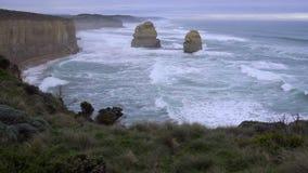 Golven die de erosie gescheurde klippen Grote Oceaanweg raken stock videobeelden