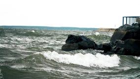 Golven die de kust raken Sterke golven die over stenen bespatten Overzeese golven die de rotsachtige kust Overzeese golven raken  stock videobeelden