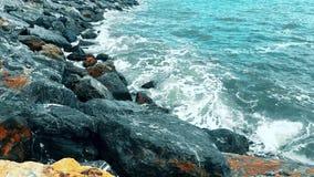 Golven die de rotsen op een zonnige dag raken stock videobeelden