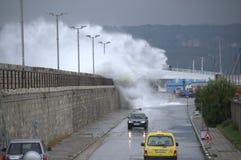 Golven die golfbreker en auto's overstromen Stock Afbeeldingen
