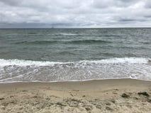 Golven die in het zand verpletteren stock afbeeldingen