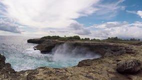 Golven die krachtige klippenberg bespatten De plaatsnaam is Duivelsscheur Tropisch eiland Nusa Lembongan, Bali, Indonesië stock videobeelden