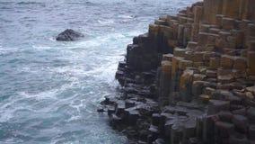 Golven die langs de Verhoogde weg van de Reus in Ierland breken stock footage
