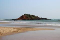 Golven die op de heuvel in het midden van het zandige strand breken stock fotografie