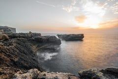 Golven die op de rotsachtige kust op een de zomerschemering verpletteren Royalty-vrije Stock Afbeelding