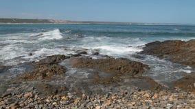 Golven die op de rotsen bij de kust verpletteren stock videobeelden