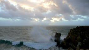 Golven die op de rotsen op de strandtunnel breken stock videobeelden