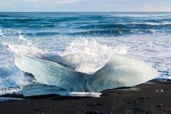 Golven die op een ijsberg op een zwart zandstrand bij Jokulsarlon-ijslagune breken, IJsland Stock Afbeelding