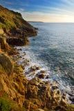 Golven die op een rotsachtig strand over Porth Nanven in de Wiegvallei breken van Cornwall, Engeland royalty-vrije stock foto