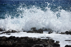 Golven die op een rotsachtig strand verpletteren Stock Foto's