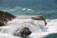 Golven die op een rotsachtige kust bespatten Stock Foto