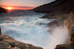 Golven die op een rotsachtige kust bij zonsondergang breken Royalty-vrije Stock Foto's