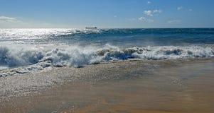 Golven die op een zandig strand breken Stock Afbeeldingen