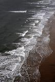 Golven die op een zandig strand breken Stock Afbeelding