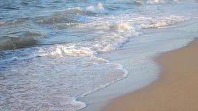 Golven die op een zandig strand omwikkelen stock video