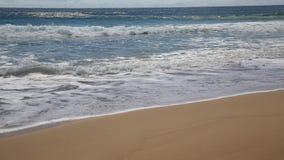 Golven die op het strand breken stock footage