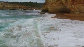 Golven die op het zandige strand rollen Lucht Mening stock footage