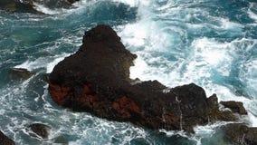 Golven die op lavarotsen verpletteren Langzame Motie stock footage