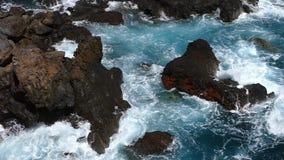 Golven die op lavarotsen verpletteren Langzame Motie stock video