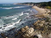 Golven die op rotsachtig strand breken Stock Foto
