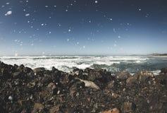 Golven die op rotsachtige kust bespatten stock foto