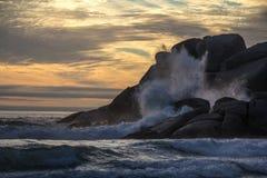 Golven die op rotsachtige kust breken Stock Foto