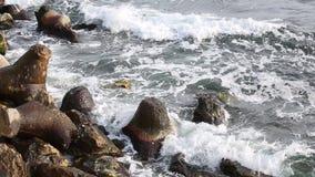 Golven die op rotsachtige kust verpletteren stock video