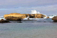 Golven die op rotsen bij kustlijn verpletteren Stock Foto's