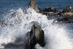 Golven die op rotsen breken royalty-vrije stock afbeelding