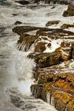 Golven die op rotsen breken stock fotografie