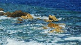 Golven die op rotsen op een zonnige dag breken stock footage